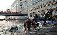30 JUN 2011 - LONDON, GBR - Competitors leave the water at the end of the swim during the women's supersprint final at the GE Canary Wharf Triathlon (PHOTO (C) NIGEL FARROW)