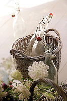 On a table in the kitchen a wicker basket, antique glass bottles and flowers from the garden are grouped together in an informal still-life