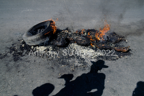 Port-au-Prince, Haiti<br /> November 25, 1987<br /> <br /> The remains of a suspected ton-ton-macoute prior to elections to be held on November 29th,  the first attempt at a democratic election in Haiti. It was unsuccessful as 34 people were killed at a polling station and elections were moved up to February 1988.<br /> <br /> Leslie Fran&ccedil;ois Manigat won the election with many political parties boycotting. He had military backing but once in office he sought greater control over the military in an effort, to fight corruption. Manigat's government was overthrown by General Henri Namphy within months.