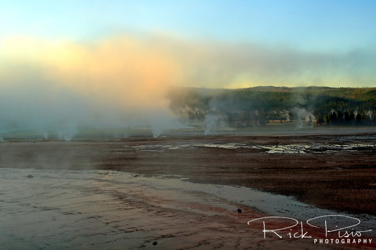 "Steam rises above the Midway Geyser Basin in Yellowstone National Park. The Midway Geyser Basin features the Grand Prismatic Spring and Excelsior Geyser. After a visit in 1899 Rudyard Kipling referred to the Midway Geyser Basin as ""Hell's Half Acre."""