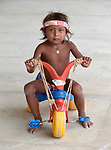 Rosaura Garcia, 4, a Warao indigenous refugee from Venezuela, rides a trike in Boa Vista, Brazil. She lives in a park invaded by Warao refugee families. They had previously been sheltered in a government refuge, but found the military-controlled environment oppressive. So they moved out and set up their own refuge in the park, where they receive some support from local Catholics.