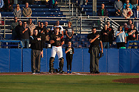 "Batavia Muckdogs catcher Jared Barnes (26) stands with a ""Star of the Game"", as well as umpires Evin Johnson (left) and Marcelo Alfonzo (right), during the national anthem before a game against the Auburn Doubledays on August 26, 2017 at Dwyer Stadium in Batavia, New York.  Batavia defeated Auburn 5-4.  (Mike Janes/Four Seam Images)"