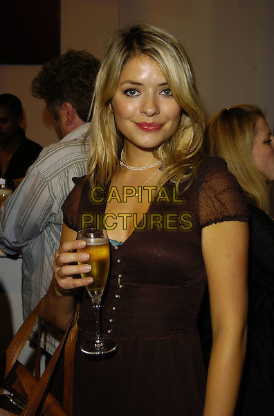 HOLLY WILLOUGHBY.At the B-Rude Show at London Fashion Week,.BFC Tent, Natural History Museum, London, .England, September 22nd 2006..half length holding glass of champagne drink red lipstick black crown dress buttons.Ref: CAN.www.capitalpictures.com.sales@capitalpictures.com.©Can Nguyen/Capital Pictures