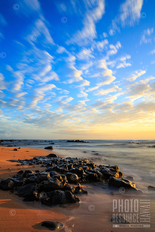 A collection of clouds roam a morning sky of blue and gold over Anahola Bay and South Aliomanu Beach, Kaua'i.