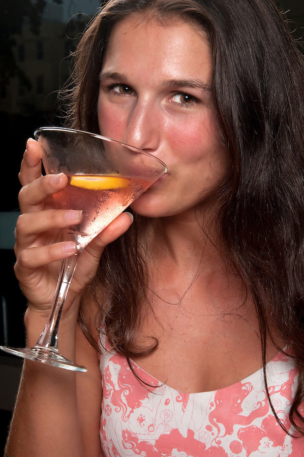 Young woman drinking a cosmopolitan cocktail in a restaurant.