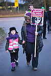 © Joel Goodman - 07973 332324 . No syndication permitted . 27/11/2013 . Manchester , UK . A woman and a young girl wave a placard at lorries leaving the site . Energy firm IGas have today (Wednesday 27th November 2013) been receiving drilling equipment in readiness for exploratory drilling at the site . Anti fracking protesters have established a camp at Barton Moss in Greater Manchester alongside an access road leading to an IGas drilling site .  Photo credit : Joel Goodman