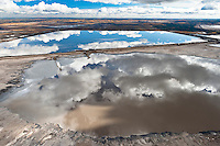 Reflected Sky in Tailings Pond.                                Northern Alberta. Canada. 2010. Disguised by the beauty of a reflection, these toxic tailings ponds are a considerable health risk. These vast toxic lakes are completely unlined and nearly a dozen of them lie on either side of the Athabasca River. Individual ponds can range in size up to 8,850 acres.      Nikon D3 70-200mm f2.8 shot at 190mm, ISO 800, 1/1600 at f4.5  Alberta Tar Sands, Northern Alberta, Canada.