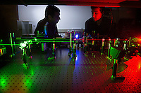 Matthew Berg (right), an assistant professor of physics and astronomy at Mississippi State, and graduate student Nava Subedi, from Nepal, lead an optical experiment to image small particles using multicolor digital holography. The technique uses laser light at several wavelengths and a color sensor to record the complex interference pattern produced by light interacting with a particle, such as pollen and mineral dust particles. The purpose of the experiment is to lay the foundation for the eventual development of a portable sensor that will characterize the particles present in the atmosphere in urban and agricultural environments.<br /> (photo by Megan Bean / &copy; Mississippi State University)