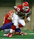 University of South Dakota's Dion Foster (33) is pulled down from behind by Winona State's Craig Martindale in the second quarter Saturday night at the DakotaDome. (Photo by Dave Eggen/Inertia)