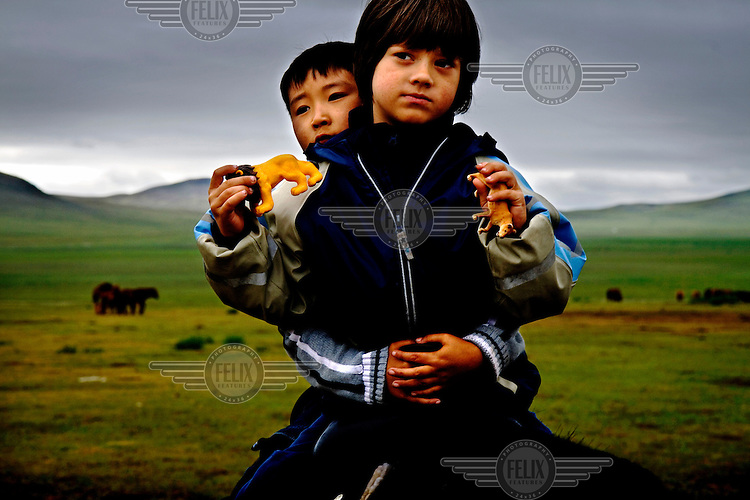"Rowan, a five-year-old autistic child, on horseback with six-year-old Bodibilguunson, the son of a guide, during a horseback expedition across Mongolia. Rowan, who has been nicknamed ""The Horse Boy"", embarked on a therapeutic journey of discovery with his parents to visit a succession of shaman healers in one of the most remote regions in the world. Following Rowan's positive response to a neighbour's horse, Betsy, and some reaction to treatment by healers, Rowan's parents hoped that the Mongolian shamanistic rituals along the route and the prolonged contact with horses would help to unlock their son's autism and assist his development.."