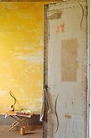 Distressed yellow-painted walls beyond an open door
