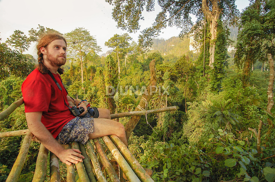 GIS specialist Shane Fryer takes in a 360 degree view from the forest canopy platform near Lake Tebo on the Sangkulirang Rapid Ecological Assessement