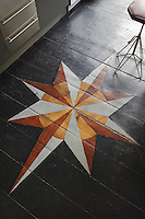 A hand-painted star is the focal point of the black-painted wood floor in the kitchen