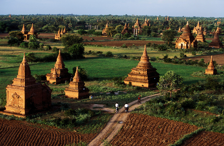 Young boys ride bicycles through the thousands of Buddhist stupas at Bagan, Burma, 2006.