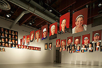 The red portraits now dominate the gallery because the black ones have been moved to the wall. Economy Portraits, a project done as Artist In Residence at Huntington Beach Art Center, in Huntington Beach, CA. <br /> <br /> Participants were asked to answer the question &quot;how has the collapse of the economy affected your life?&quot; The portraits were taken on Red, White, and Black backgrounds. The answers were printed on the portrait in the person's own handwriting. They were suspended from fishing line throughout the gallery until enough were printed to build an American flag on the wall.