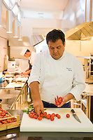 Portrait of chef Gennaro Esposito selecting tomatoes for chopping in the kitchen of his restaurant