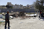 A Palestinian man walks past the remains of his shed after demolished by Israeli bulldozers, in al-Tour neighborhood, east Jerusalem on April 29, 2014. Israeli forces accompanied by bulldozers, stormed Al-Hardub neighborhood at al-Tur neighborhood in Jerusalem, and proceeded to demolish two residential sheds which housed eight family members, leaving them without a home. Two youths were arrested during the demolition of the sheds. Photo by Saeed Qaq