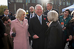 Prince Charles and Camilla the Duchess of Cornwall at the Swiss Cottage farmers market, meeting stall holders. Charles relaxed and laughing, Camilla with a cake cutter. Body guards are standing behind them. Its is the 20th anniversary of London Farmers Market.   UK 2019.