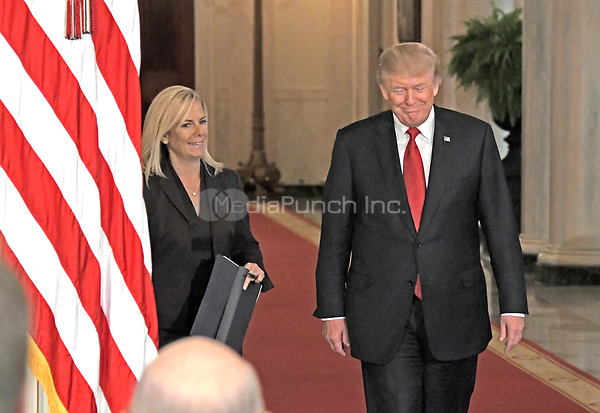 United States President Donald J. Trump, right, arrives to announce he will name Principal Deputy White House Chief of Staff Kirstjen Nielsen, left, as Secretary of Homeland Security in the East Room of the White House in Washington, DC on Thursday, October 12, 2017.  If confirmed, Nielsen will replace Acting US Secretary of Homeland Security Elaine C. Duke, who has been in that position since General John F. Kelly, USMC (Retired) resigned to become White House Chief of Staff.<br /> Credit: Ron Sachs / CNP /MediaPunch