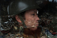 A Japanese Self Defence Force (SDF) soldier looks out at the devastation reflected in the window. Thousands of people died in this small town which ran out of body bags. On 11 March 2011 a magnitude 9 earthquake struck 130 km off the coast of Northern Japan causing a massive Tsunami that swept across the coast of Northern Honshu. The earthquake and tsunami caused extensive damage and loss of life.