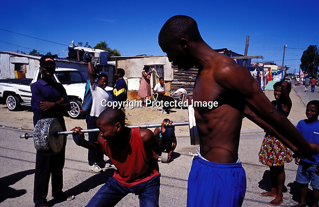 dippchi00319.Digital. People. Children. Boys lifting weights in the street in Site C section of Khayelitsha, South Africa on November 2, 2003. Townships, sport, lifestyle, poverty, shacks, activity. .©Per-Anders Pettersson/iAfrika photos