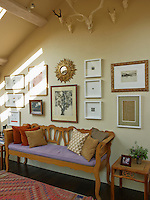 A corner of the family room houses a varied collection of prints and paintings including pieces by Gwen Raverat