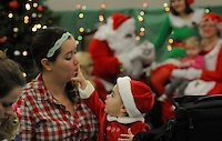 STAFF PHOTO FLIP PUTTHOFF <br /> BREAKFAST WITH SANTA<br /> Megan Neal of Cave Springs has help eating a donut from her daught Rayden Neal, age 16 months, during Breakfast with Santa on Saturday Dec. 6 2014 at the Rogers Public Library. Children and adults visited with Santa and enjoyed donuts at the event. There was also craft making and cartoons with a Christmas theme.