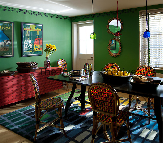 An eclectic dining room with a black wood dining table with french cafe chairs custom colour made by Maison Gatti. The Christopher Farr rug is designed by Sarah Morris whose  patterns are based on the reflections of New York sky scrapers. The green walls are in Fennel Green by Sanderson and decorated with stencils by fashion textile designer Sarah Pasricha to compensate for the lack of architectural features in thid basement room. The bold colours in this room are complimented with framed posters and lamps by Emery et Cie.