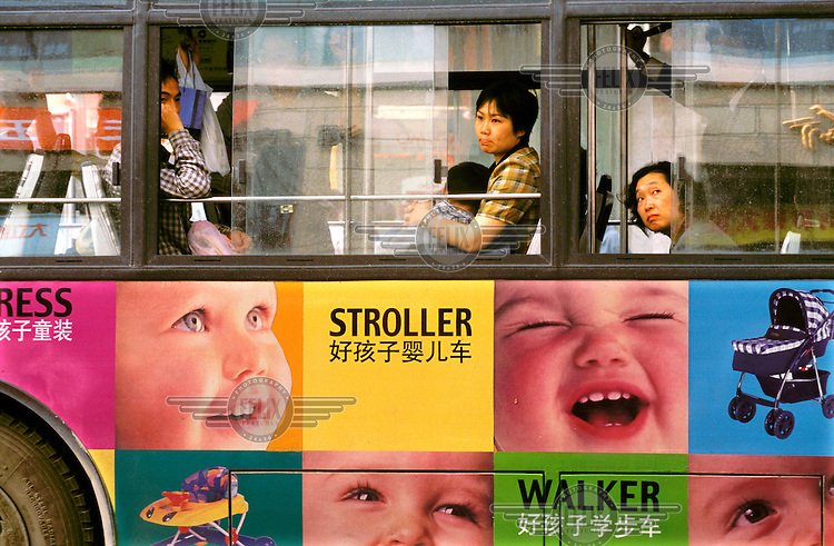 Mark Henley/Panos Pictures..CHina, Shanghai..Mther and her child on bus with advertising for baby products...