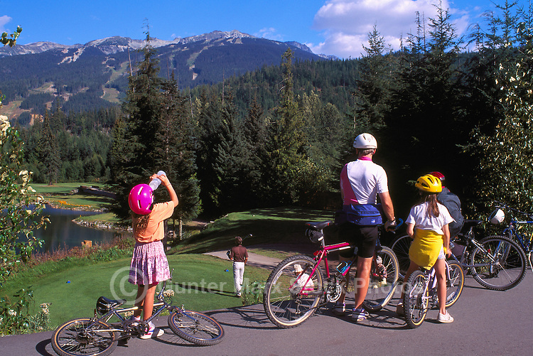 Family cycling with Bicycles stop to look at Golf Course and Blackcomb Ski Runs, Whistler, BC, British Columbia, Canada, Summer