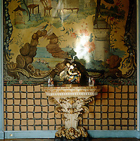 In front of a painted Chinese panel in the dining room an elaborate console table displays a Chinese porcelain sculpture flanked by two small vases in the shape of monkeys