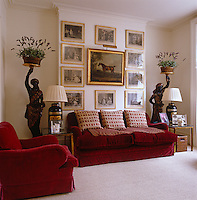In the sitting room the armchair and sofa are upholstered in red velvet and a series of Hogarth's engravings surrounding a 19th century equestrian portrait line the wall