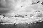 Female youth aged 5-10 years old standing alone in a summer field with long grass under a sky with white clouds