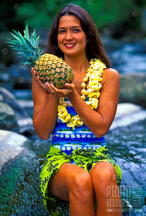 Woman sitting on a rock and wearing a plumeria lei holds up a pineapple.