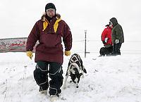 Veteran Iditarod musher Palmer Sagoonick, now a volunteer checker, walks a dropped dog to a waiting plane in Shaktoolik Monday.