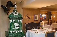 urope/Italie/Trentin Haut-Adige/Dolomites/Alta Badia/ San Cassiano: Restaurant St Hubertus à l'Hotel Rosa Alpina détail de la salle de restaurant avec son poêle en faïence sous le signe du cerf