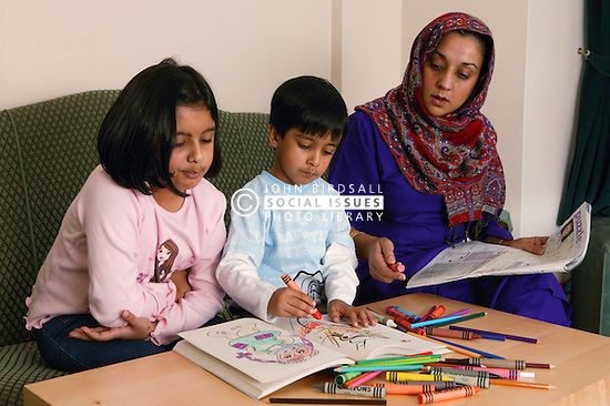 Single parent helping her young children with colouring book,