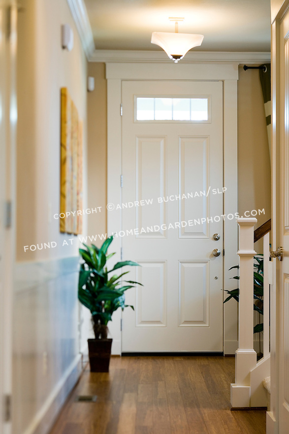 A skewed focus image of the inside view of a white, overheight front door with window panes at the top, a newel post and banister coming from upstairs, and hardwood floors below.