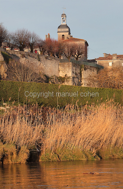 The river bank, and above, the church and medieval walls of the ancient village of Bourg, built in Roman times at the confluence of the Dordogne and Garonne rivers, on the Gironde Estuary, Aquitaine, France. Picture by Manuel Cohen