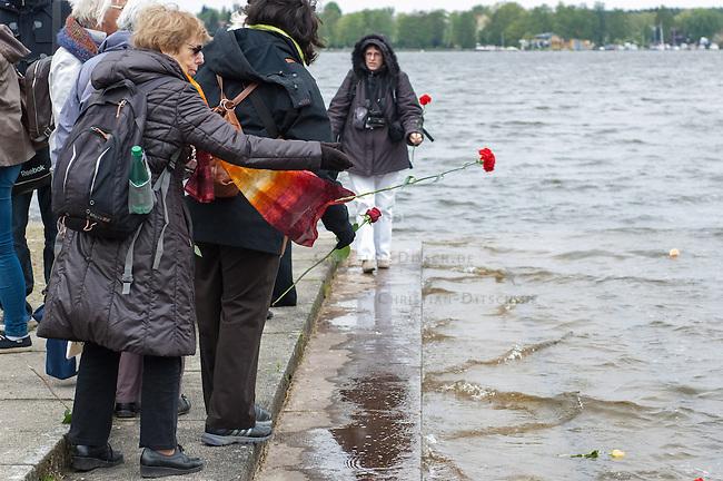 Feielichkeit zum 69. Jahrestag der Befreiung des Frauenkonzentrationslager Ravensbrueck.<br />Am Sonntag den 4. Mai 2014 fand die im ehemaligen Frauenkonzentrationslager Ravensbrueck die Feierlichkeiten zum 69. Jahrestag der Befreiung statt.<br />In Ravensbrueck war von 1938 bis 1945 ein Konzentrationlager fuer Frauen in der brandenburgischen Kleinstadt Fuerstenberg. Im Mai 1945 wurde es von russischen Soldaten befreit.<br />Zu den Feierlichkeiten kamen ueberlebende Frauen aus ganz Europa, die meissten von ihnen aus Polen.<br />Im Bild: Teilnehmer der Feierlichkeit werfen zum Gedenken an die Ermordeten Frauen Blumen in den See am ehemaligen KZ.<br />4.5.2014, Ravensbrueck/Fuerstenberg<br />Copyright: Christian-Ditsch.de<br />[Inhaltsveraendernde Manipulation des Fotos nur nach ausdruecklicher Genehmigung des Fotografen. Vereinbarungen ueber Abtretung von Persoenlichkeitsrechten/Model Release der abgebildeten Person/Personen liegen nicht vor. NO MODEL RELEASE! Don't publish without copyright Christian-Ditsch.de, Veroeffentlichung nur mit Fotografennennung, sowie gegen Honorar, MwSt. und Beleg. Konto: I N G - D i B a, IBAN DE58500105175400192269, BIC INGDDEFFXXX, Kontakt: post@christian-ditsch.de]