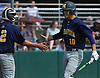 Johnny Castagnozzi #10 of Massapequa, right, gets congratulated after crossing home plate in the top of the second inning of the Nassau County varsity baseball Class AA final against Oceanside at SUNY Old Westbury on Saturday, May 26, 2018. Massapequa won 6-5 to take Game 1 of the best-of-three series.