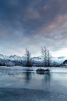Winter landscape of frozen Knik River and frost-covered trees with Chugach Mountains at sunrise. reflection on ice frozen river<br /> <br /> Photo by Jeff Schultz/SchultzPhoto.com  (C) 2018  ALL RIGHTS RESERVED
