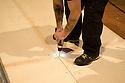 A worker with tattooed arms, fixed panels of a footboard with an electric screwdriver at Fassbinder Hall of Elfo-Puccini Theatre, Milan. © Carlo Cerchioli..Un operaio, con le braccia tatuate, fissa i pannelli di una pedana con un avvitatore elettrico alla sala Fassbinder del Teatro Elfo-Puccini, Milano.