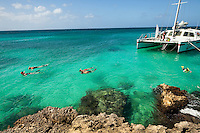 A catamaran sailing ship waits in the waters of Aruba's Malmok beach while its passengers snorkel along the west coast of Aruba.  Aruba remains a popular tourist destination, with international planes and cruise ships arriving daily. Aruba, part of the Lesser Antilles, is famous for its white sand beaches, blue/green waters and mild climate.