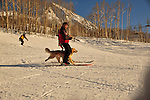 Crested Butte ski patrolman Russ Reycraft skiing with his avalanche rescue dog, Betty.  She is trained to run behind his back legs, to avoid being harmed by other skiers and boarders on the mountain.