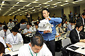 May 20th, 2011, Tokyo, Japan - A staff member of Tokyo Electric Power Co. distributes papers for the media before a news conference at its head office in Tokyo on Friday, May 20, 2011. The utility company, known as TEPCO, logged a fiscal-year net loss of $15.28 billion, the biggest annual loss in Japanese corporate history outside the financial sector, from the crisis at its Fukushima No. 1 nuclear power plant, which has been crippled since the March 11 earthquake and tsunami. Shimizu, 66, said he will step down to take responsibility for damaging the public's trust and causing inconvenience. (Photo by Natsuki Sakai/AFLO) [3615] -mis-