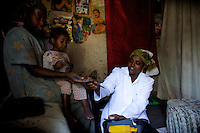Haisalle, 35 years old, ( with white uniform ) nurse supervisor for the home base care volunteers in Debre Zheit  visits  two beneficiaries living with HIV  during a visit  supported by the american NGO Save the Children US along the high risk corridor  in Debre Zheit, Ethiopia on tusday March 10 2009..Save the Children US manages a vaste rrange of activities in support of vulnarable people that live along the truck route that connects Addis Ababa, Ethiopia's capital to the port of Djibouti. Ethiopia, a land locked country, depends on the Djibouti port for most of its imports and exports.