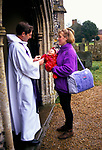 Revd Martin Down welcomes parishioners to a traditional Sunday morning church service at St. Nicholas. Ashill, Norfolk. UK