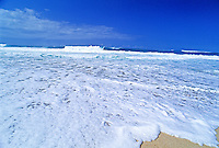 A large wave breaking on Oahu's North shore creates a huge swath of white frothy foam covering the shoreline. A milky white cloud mirrors the image above.