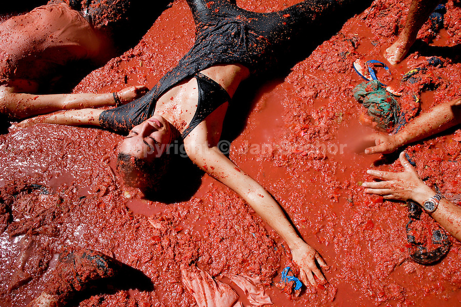 A girl lies in tomato pulp during La Tomatina festival in Bunol, Spain, 31 August 2006. La Tomatina is a tomato fight held annually in the town of Bunol, close to Valencia. Approximately 40,000 people from all over the world arrive to fight in the battle in which about 50 tons of over-ripe tomatoes are thrown in the street. During the one hour battle everybody fights everybody by throwing squashed tomatoes. The origin of this event is unknown but the Tomatina fights have been recorded since 1945.